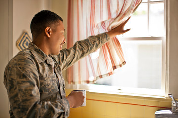 Smiling young adult soldier holding a mug while looking out the window of his home.