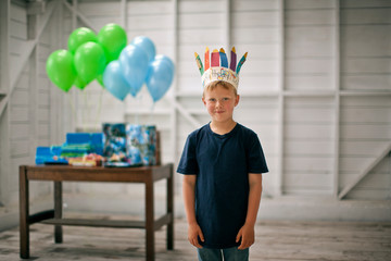 Portrait of a young boy standing in front of a table of presents and balloons.