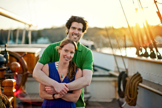 Married couple standing together on ship's deck.