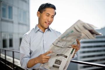 Businessman reading newspaper on balcony.