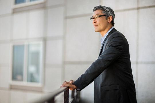 Pensive mature businessman taking a break on a balcony.