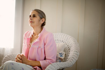Contemplative senior woman sitting in an armchair with her hands clasped.