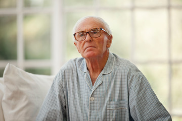 Concerned senior man wearing pajamas inside a rest home.
