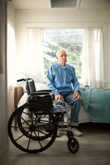 Contemplative senior man sitting on the edge of his bed next to a wheelchair.