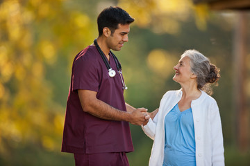 Smiling senior woman and a male doctor having a conversation while holding hands in a park.