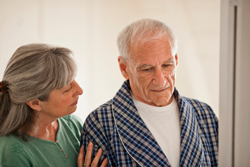 Senior woman comforting her unwell husband.