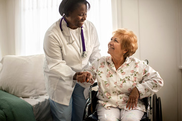 Smiling female doctor having a conversation with an elderly female patient sitting in a wheelchair.