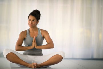 Relaxed young woman sitting cross-legged on a yoga mat.