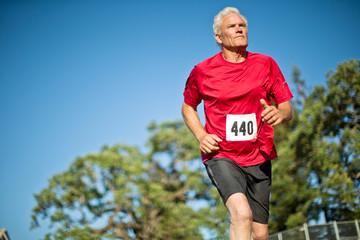 Active senior man running on a sports track.