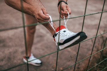 Close-up of a man's leg tying shoelaces on a shoe, in summer in the city about a fence or fence. Sports lifestyle workout, jogging in morning in evening, guy doing fitness.