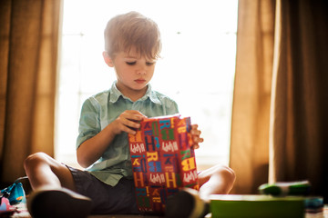 Young boy opening birthday presents.