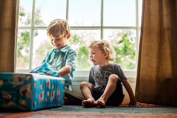 Young boy opening birthday presents while his brother watches.