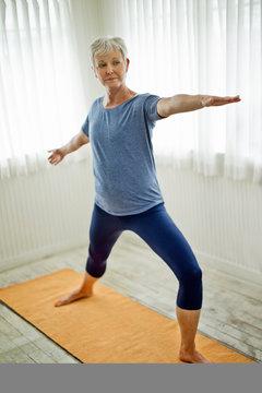 Mature woman practicing yoga on mat.