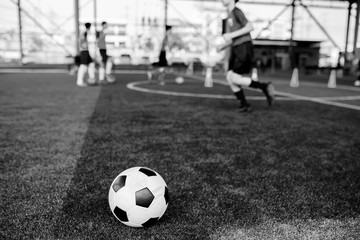black and white picture of football on artificial turf