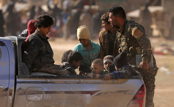 Children from the Yazidi community, who were recently freed after being captured by Islamic State fighters, ride on a back of a truck near Baghouz