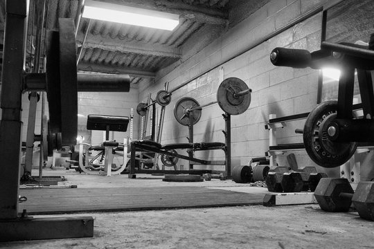 Black and white photo of a dirty, grungy ,hard core, weight room ,gym.Work out Room.