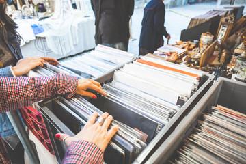 Papiers peints Magasin de musique girl choosing discs in cosmopolitan city street market