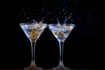 Two martinis with splashing olives