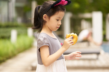 Delicious taste expression of little asian girl portrait .