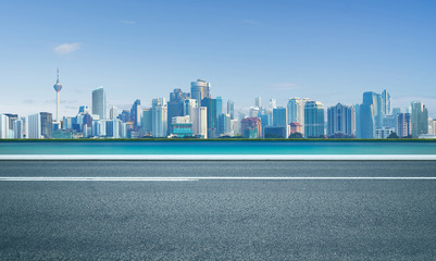 Road with sea and cityscape skyline , morning scene .