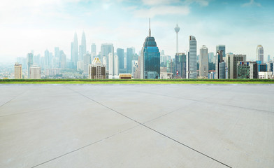 Empty concrete cement floor with green and cityscape skyline , morning scene .