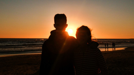 a Shadow couple of lovers enjoying a lovely beach sunset background