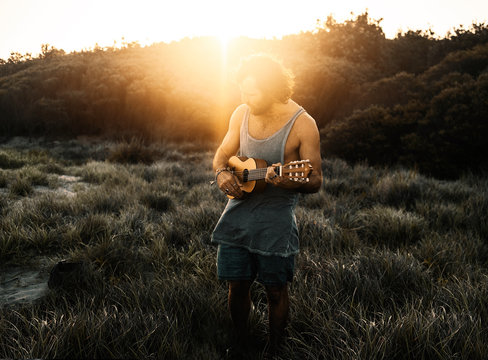 Man playing guitar in nature at sunset