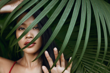 Beauty. Beautiful asian woman with palm leaf over face in nature