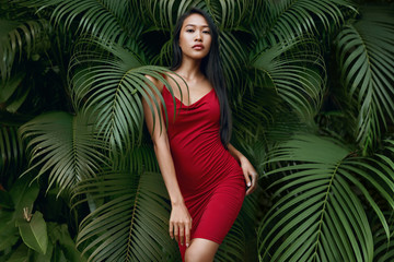 Fashion. Woman model in red dress with green palm leaves