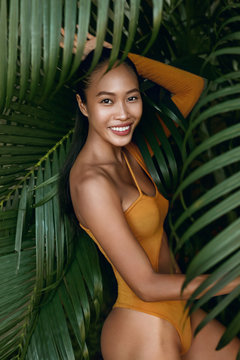 Summer fashion. Happy woman model in swimsuit at tropical nature