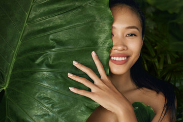 Beauty face. Woman model with natural makeup behind green leaf