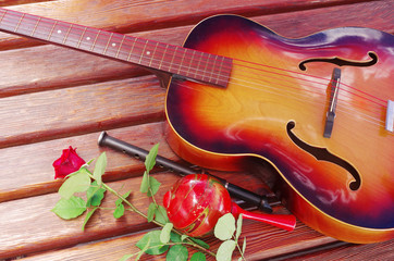 Acoustic guitar, maracas, pipe and red rose on a wooden table.
