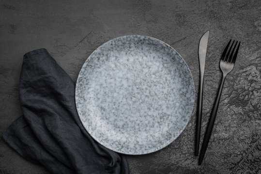 Stylish table setting with black cutlery. Empty plate, table textile and black cutlery on black concrete background. Top view. Restaurant, menu, cafe or food concept