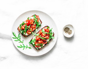 Tomatoes and arugula salad whole grain bread sandwiches on a light background, top view. Copy space