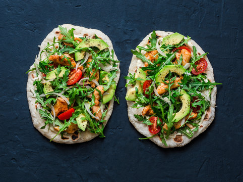 Pan-fried flatbread chicken, avocado, tomatoes, arugula pizza on dark background, top view