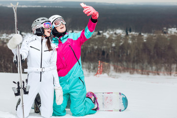 two beautiful women shooting a video during winter holiday, blogger at resort, sportswomen are resting on a warm winter day