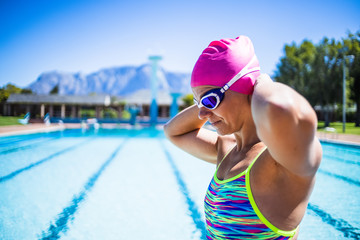 Close up image of a beautiful female swimmer in a swimming pool getting ready to train.