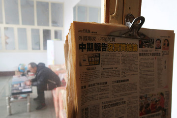 Newspapers with articles on the missing Malaysia Airlines flight MH370 hang by a window as Li Eryou looks at a photo album during a Reuters interview at his house in Handan