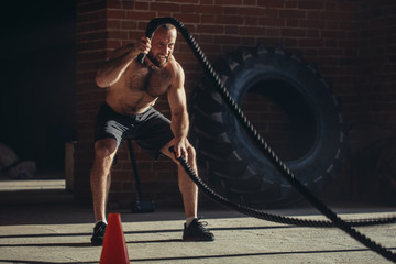 Sport concept. Caucasian athlet with naked torso with rope in functional training at outdoor gym in a crossfit workout over brick wall background.