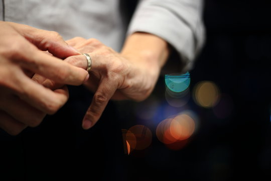 man putting on wedding ring. close up shot of man fidgeting ring with nice out of focus urban light backgrounds.