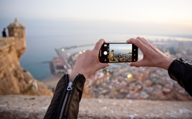 A person takes pictures with a smartphone from a viewpoint of Alicante