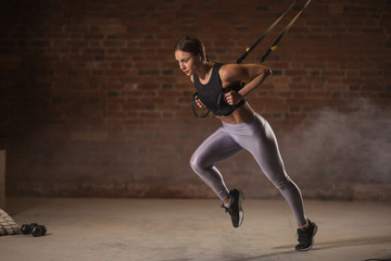 Female gymnast doing upper body exercise using elastic straps against brick wall background in gym....