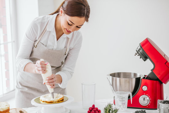pleasant gorgeous woman gets pleasure from cooking cake. close up photo. copy space