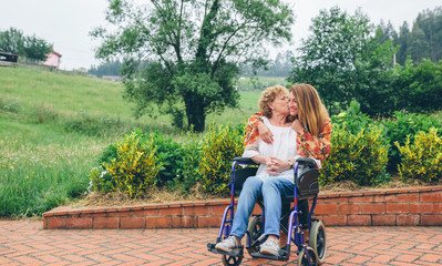 Woman in a wheelchair kissing her daughter