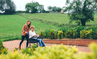 Woman carrying her mother in a wheelchair