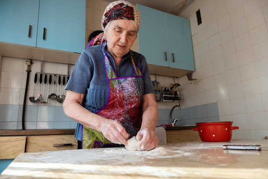 Senior woman kneading the dough in her home kitchen, grandmother cooking bakery products, fresh bread, tasty pie