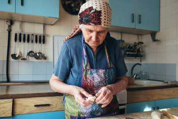 Grandmother cooking, preparing sweet dumpling with cottage cheese