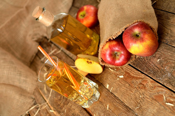 Apple juice, red apples, straw and bottle in background on rustic wooden boards
