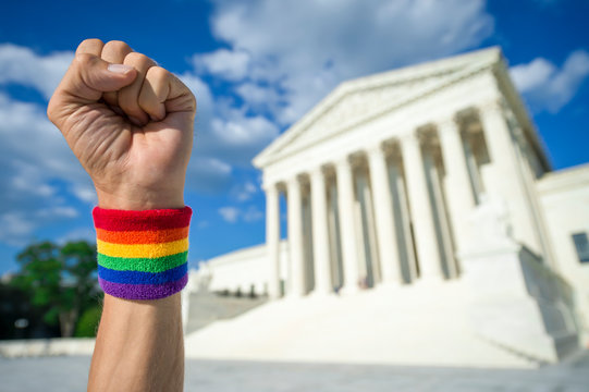 Hand wearing gay pride rainbow wristband making a power fist gesture outside the Supreme Court building in Washington, DC, USA