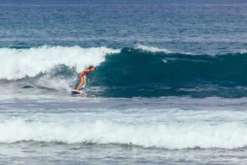 Young asian woman in green bikini surfing turquoise wave in Bali